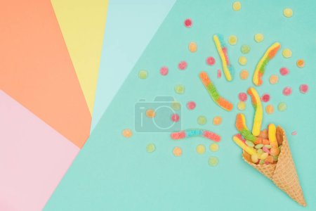 Photo for Top view of scattered tasty jelly candies and waffle cone on colored surface - Royalty Free Image