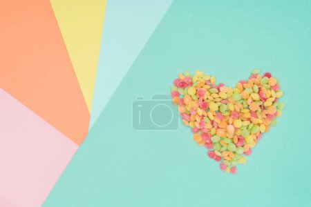 top view of jelly candies in shape of heart on colored surface