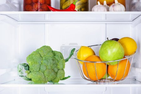 broccoli and ripe tasty fruits in fridge