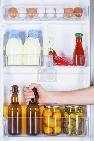 cropped image of man taking bottle of beer from fridge