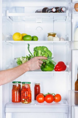 Photo for Cropped image of man taking broccoli from fridge - Royalty Free Image