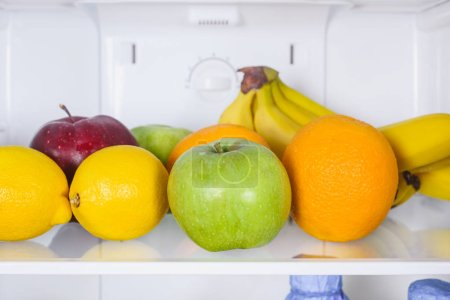 close up of apples, oranges and bananas in fridge