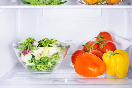 bowl of salad and ripe bell peppers in fridge