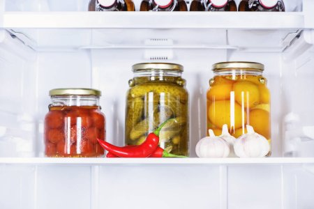 Photo for Preserved vegetables in glass jars and ripe chili peppers in fridge - Royalty Free Image