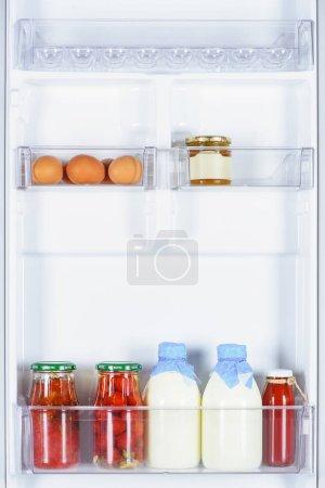 eggs, preserved tomatoes and bottles of milk in fridge