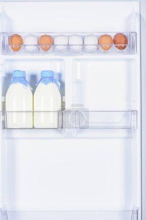 chicken eggs and bottles of milk in fridge