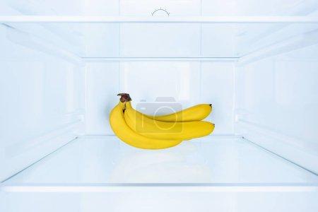 ripe tasty bananas on shelf in fridge