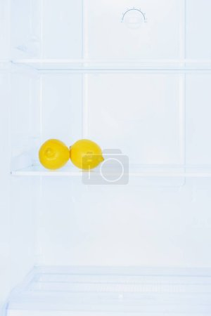two ripe lemons on shelf in fridge