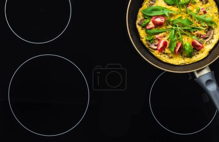 Photo for Top view of omelette in frying pan cooking on black stove - Royalty Free Image