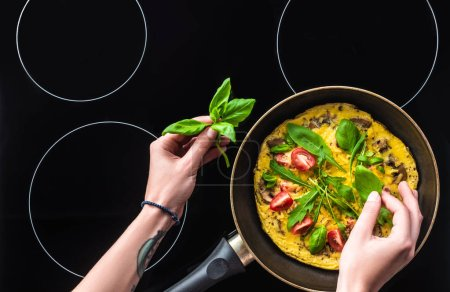 Photo for Cropped shot of woman cooking omelette in frying pan on black stove - Royalty Free Image
