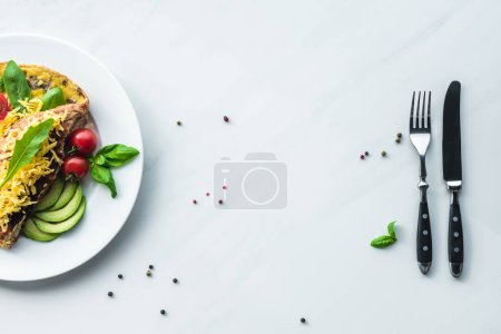 Photo for Top view of healthy omelette for breakfast and cutlery on white marble surface - Royalty Free Image
