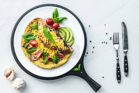 food composition with healthy omelette on wooden board and cutlery on white marble tabletop