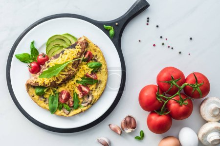 food composition with healthy omelette on wooden board and ingredients on white marble tabletop
