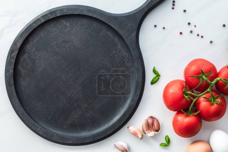 top view of wooden board, vegetables and raw chicken eggs for cooking omelette on white marble tabletop