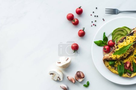 Photo for Top view of homemade omelette with cherry tomatoes, avocado pieces and cutlery on white marble surface - Royalty Free Image