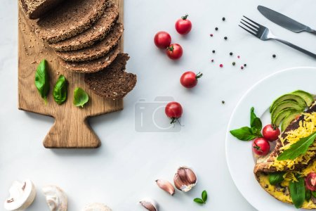 Photo for Flat lay with cooked omelette, vegetables and bread on wooden cutting board arranged on white surface - Royalty Free Image