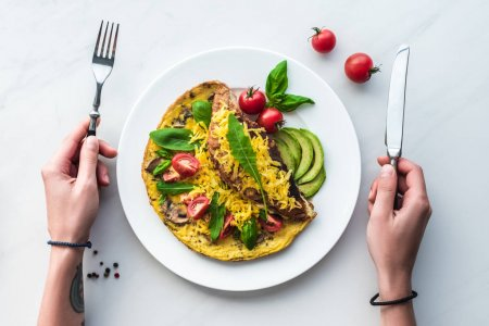 Photo for Partial view of woman with cutlery in hands at tabletop with homemade omelette for breakfast - Royalty Free Image