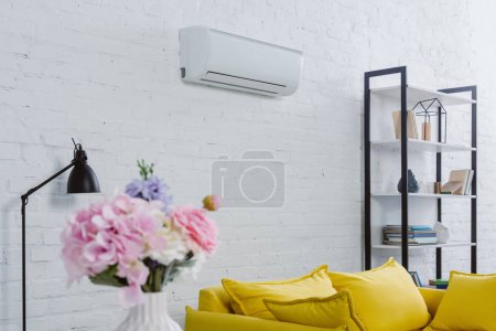 interior of modern living room with flowers in vase, yellow couch and air conditioner hanging on white wall
