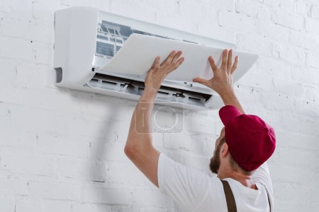 close-up shot of young repairman fixing air conditioner hanging on white brick wall