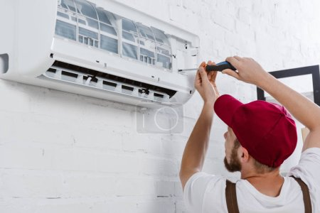 close-up shot of professional repairman changing filter for air conditioner with screwdriver