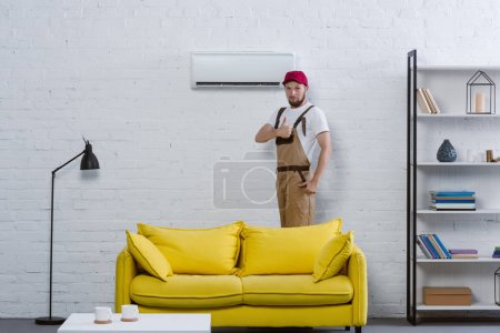 professional repairman standing near air conditioner at living room and showing thumb up