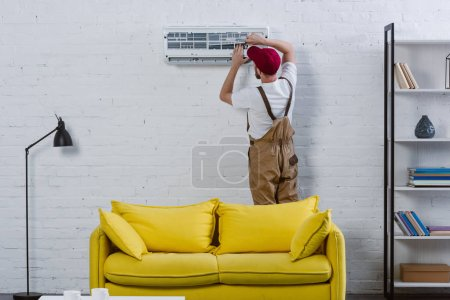 professional repairman fixing air conditioner hanging on white brick wall