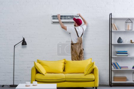 young professional repairman fixing air conditioner hanging on white brick wall