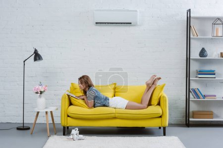 beautiful young woman reading book on sofa under air conditioner hanging on wall