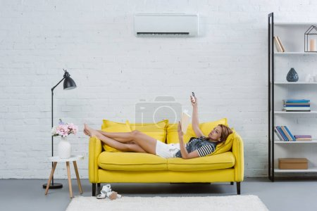 attractive young woman reading book on sofa and pointing at air conditioner with remote control