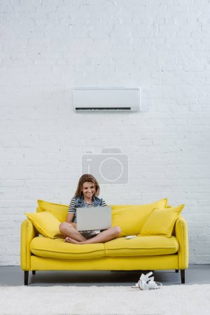 attractive young woman working with laptop while sitting on couch under air conditioner hanging on wall