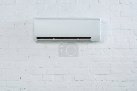 front view of air conditioner hanging on white brick wall