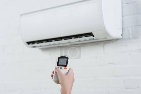 cropped shot of woman pointing at air conditioner hanging on white brick wall with remote control