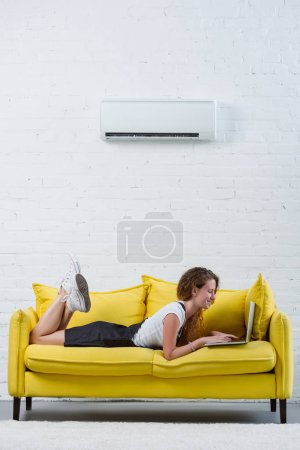 happy young woman working with laptop while lying on couch under air conditioner hanging on wall