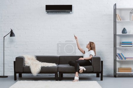 beautiful young woman sitting on sofa and pointing at air conditioner hanging on wall with remote control