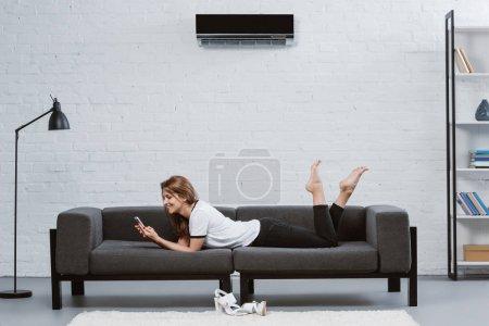 Foto de Mujer joven feliz con smartphone mientras está acostado en el sofá con aire acondicionado, colgado en pared - Imagen libre de derechos