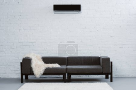 air conditioner hanging on white brick wall at living room