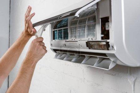 Photo pour Recadrée tir du réparateur qui décollait le filtre de climatiseur - image libre de droit