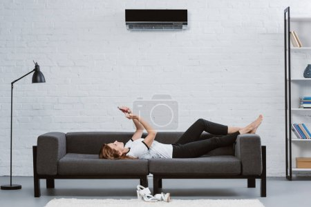 happy young woman using smartphone on sofa under air conditioner hanging on wall