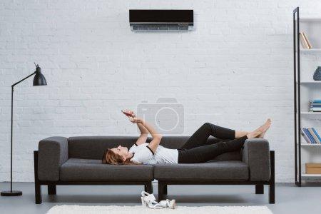Foto de Mujer joven feliz con smartphone en sofá bajo aire acondicionado colgar en la pared - Imagen libre de derechos