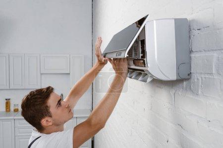Photo pour Réparateur décoller filtre sale de climatiseur accroché au mur de briques blanches - image libre de droit