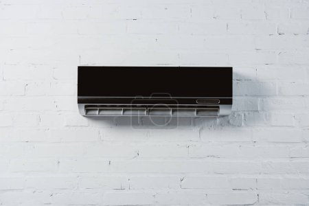modern air conditioner hanging on white brick wall