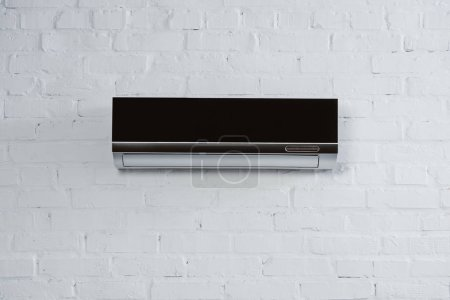 modern black air conditioner hanging on white brick wall
