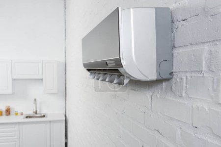 close-up shot of air conditioner hanging on white brick wall