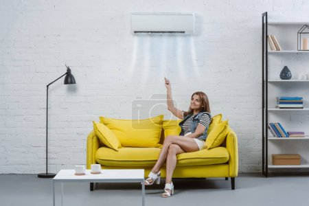 attractive young woman pointing at air conditioner hanging on wall with remote control