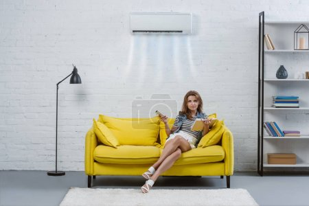 beautiful young woman with book sitting on couch and pointing at air conditioner hanging on wall with remote control