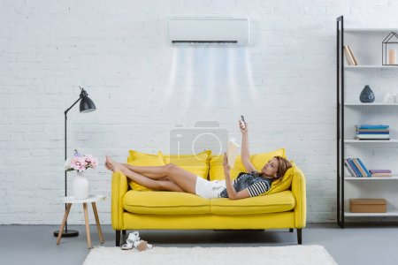 concentrated young woman reading book on couch and pointing at air conditioner hanging on wall with remote control