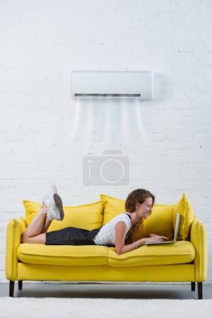 Photo pour Attrayant jeune femme travaillant avec ordinateur portable sur le canapé sous climatiseur suspendu au mur - image libre de droit