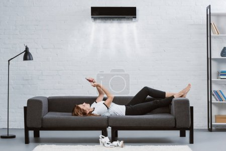 relaxed young woman using smartphone on couch under air conditioner hanging on wall