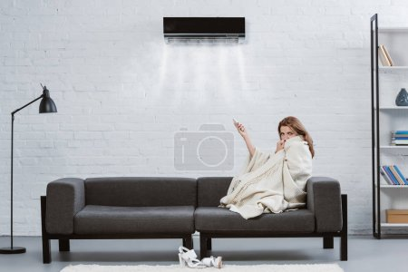 jeune femme recouverte de couverture sur le canapé sous climatiseur accroché sur le mur et soufflant refroidi par air