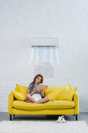 focused young woman reading book on couch under air conditioner hanging on wall and blowing cooled air